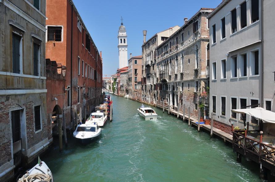 Падающая башня, канал и домики на водой.