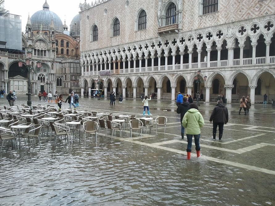 Туристы меряют лужи на площади Святого Марка.