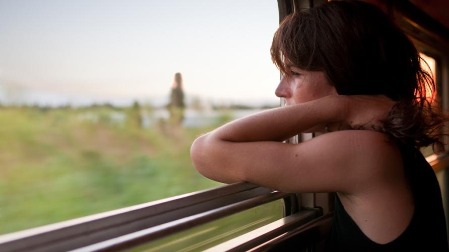 девушка смотрит в окно вагона фото