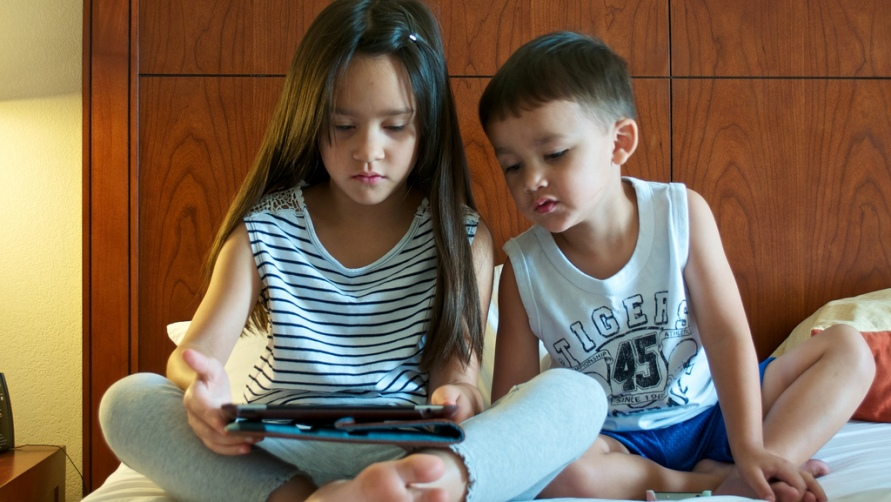 Дети играют в планшет.